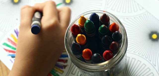 יד של ילד אוחזת בצבע ולימינו צבעים נוספים