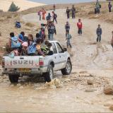 ילדים נוסעים בטנדר פתוח בכביש מוצף בנגב