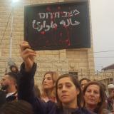 """אישה ערביה מניפה שלט בהפגנה ועליו כתוב """"מצב חירום"""""""