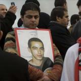 גבר מחזיק תמונת נער מת בהפגנה